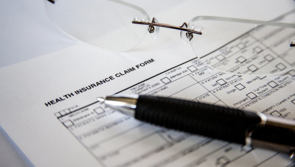 Health insurance form with pen and a pair of glasses